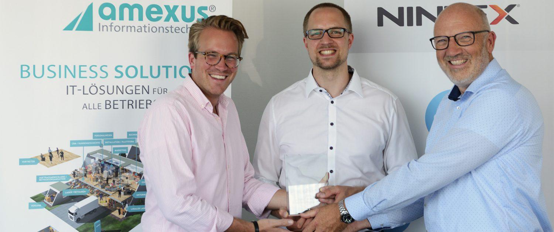 Kevin Moran, Senior Partner Manager bei Nintex, überreicht amexus Mitarbeiter Dominik Stange und Geschäftsführer Stefan Nacke den Nintex Partner Award.